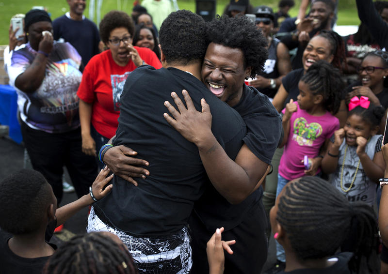 Mike Hassell, of the Chosen for Change foundation, hugs Joshua Anderson, of the Get Fit Crew, after a dance-off at a party to celebrate what would've been Mike Brown's 20th birthday on May 20, 2016 at Canfield Green Apartments.