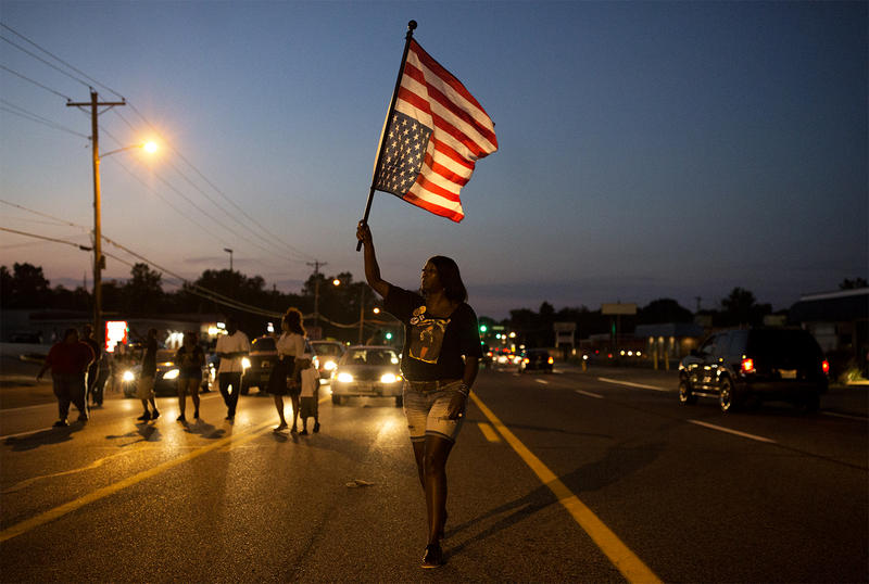 Protesters walk down West Florissant Avenue in Ferguson on Aug. 9, 2016, two years after Mike Brown was killed by a Ferguson police officer.