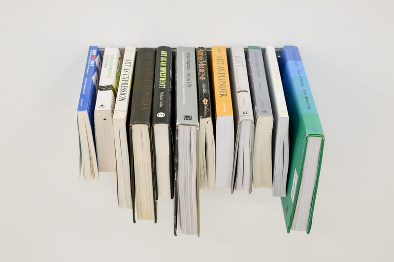 """Sarrita Hunn's Sarrita Hunn, """"Art As...Library""""  is a number of books attached at thier ends, spine up to the wall, was displayed at an earlier exhibit celebrating Temporary Art Review's fifth anniversary."""