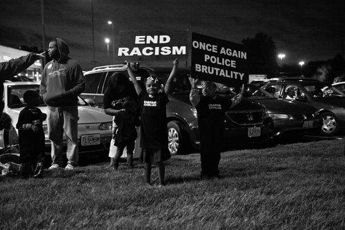 Children hold anti-rascist signs while standing on the lawn at a Ferguson related protest.