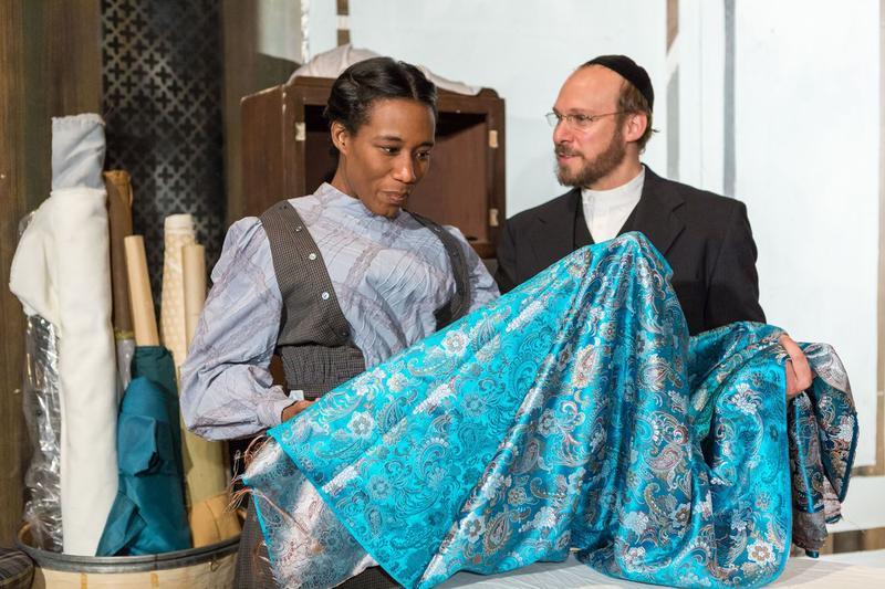 File photo: Esther, played by Jacqueline Thompson, and Mr. Marks, played by Jim Butz, examine a bolt of fine fabric in a scene that simmers with largely unspoken feelings.