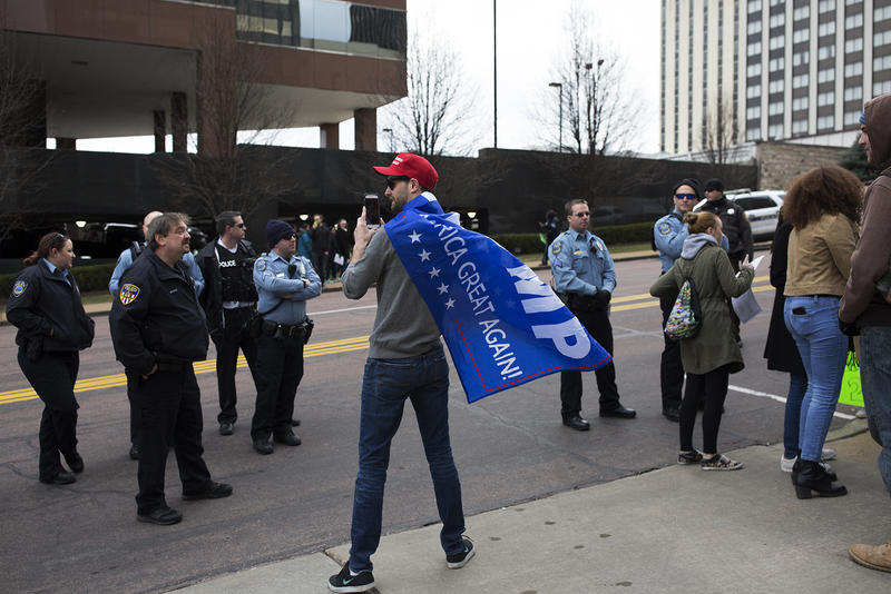 A lone Trump supporter takes a video of police and protesters at the end of the rally.