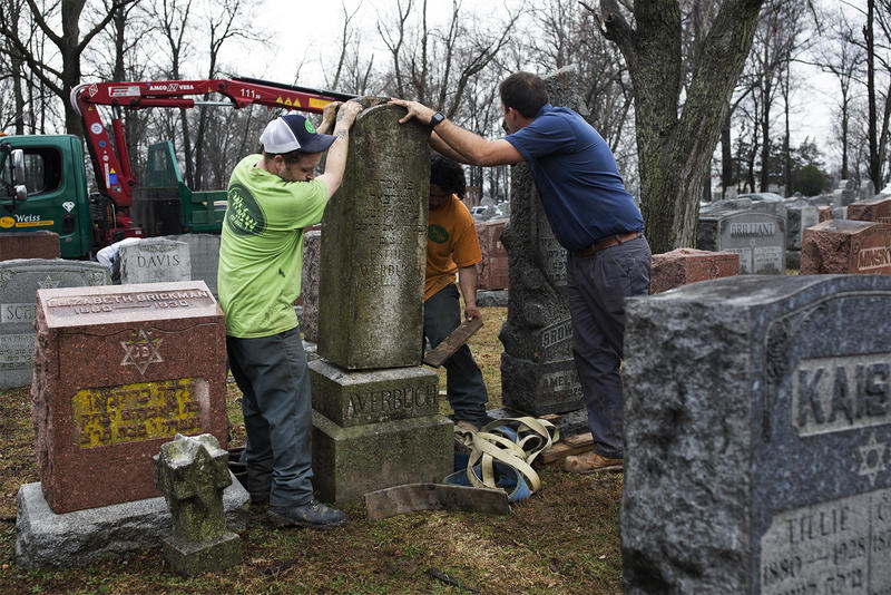 Workers with Rosenbloom Monuments Company re-set headstones at Chesed Shel Emeth Cemetery on Tuesday morning. (Feb. 21, 2017)