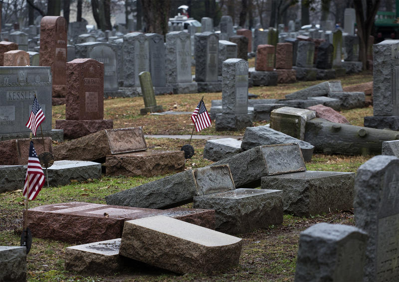 Many headstones remained toppled over Tuesday morning as crews worked to re-set them.