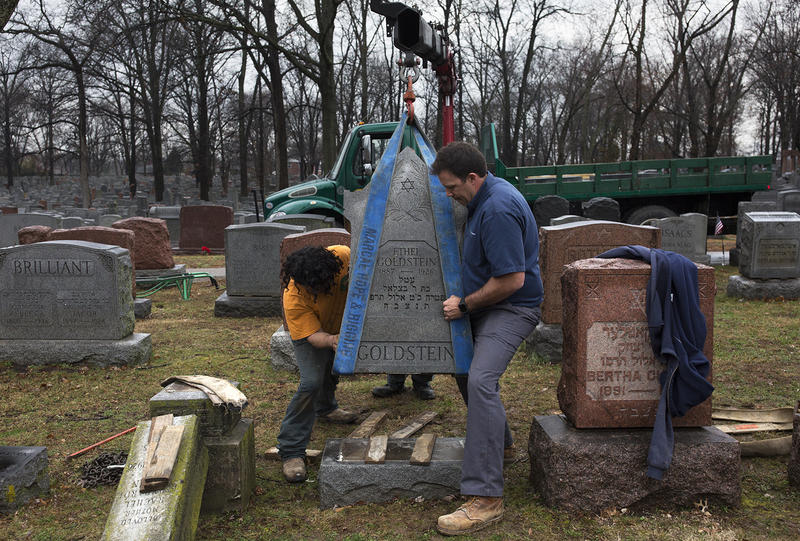 Crews with Rosenbloom Monuments Company lift headstones back onto their bases in February, 2017.