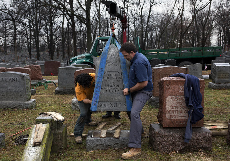 Workers with Rosenbloom Monuments Company re-set headstones at Chesed Shel Emeth Cemetery on Tuesday morning.