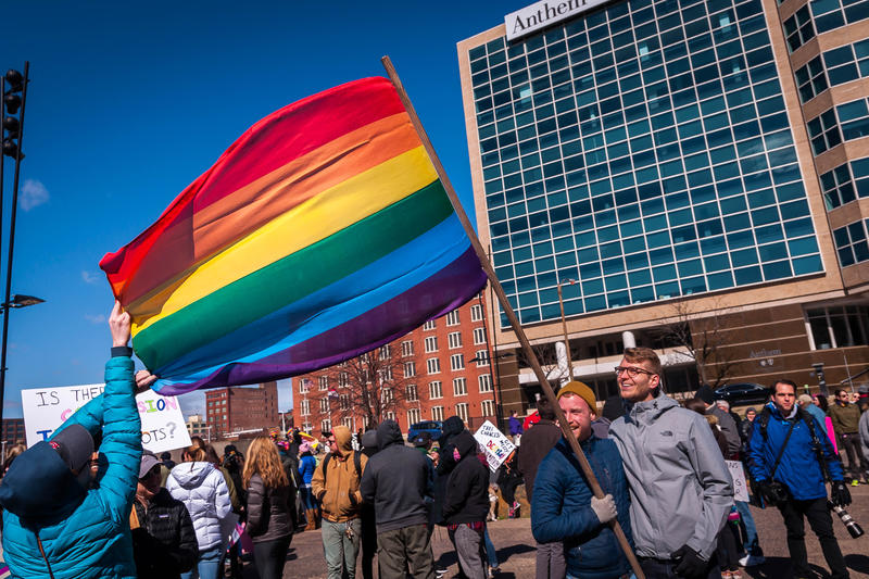 Janie Oliphant, left, fixes a LGBT rights flag held by Cody Copp and Samuel Taylor so they can have their picture taken at a rally and march in St. Louis on Saturday, Feb. 25, 2017.