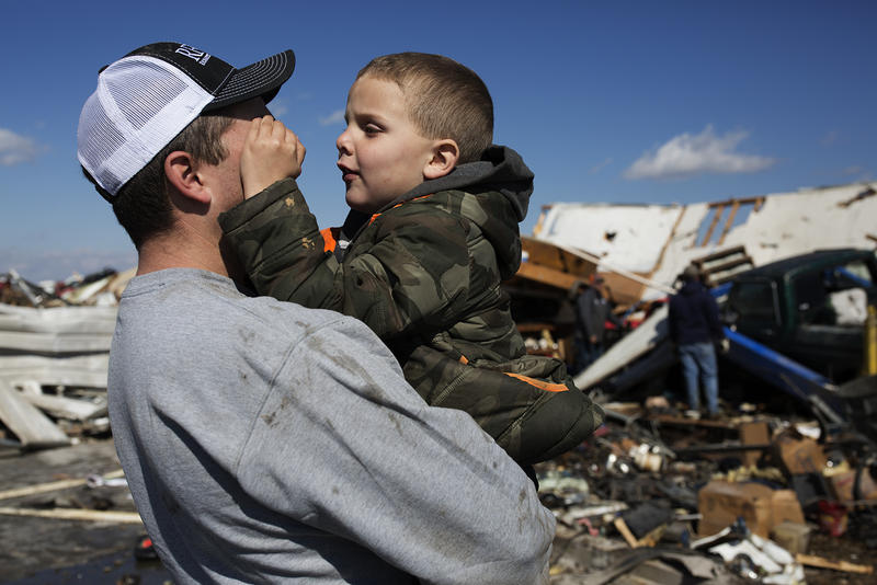 Tyson Richardet holds his son, Kwinton, 5, while surveying the damage to his auto body shop. (Perryville, March 1, 2017)