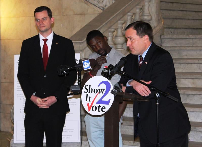 Three men stand at a podium with microphones at St. Louis City Hall.