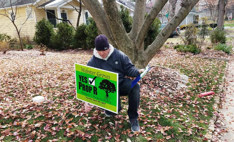 Webster Groves fire Capt. Jason Simpson puts a sign in the yard of a Proposition R supporter on March 12, 2017. Prop R is one of several public safety tax increases on the St. Louis County ballot in April.