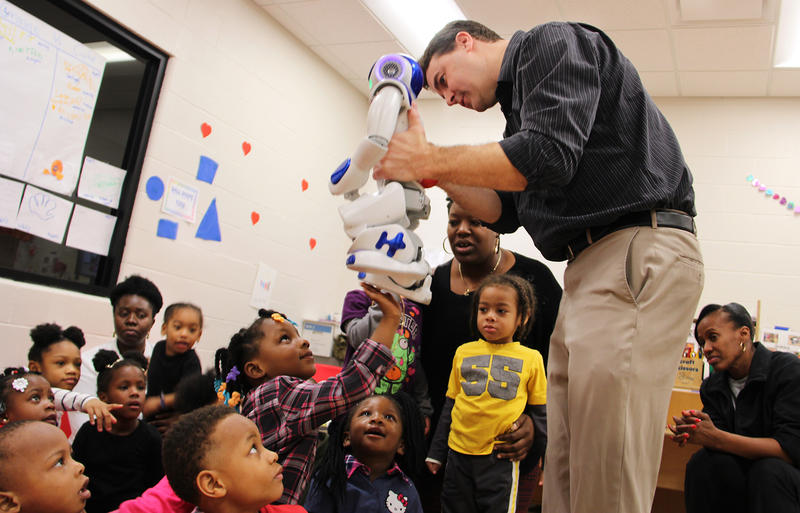 SIUE psychology professor Stephen Hupp lets a class of preschoolers at the Jackie Joyner-Kersee Center in East St. Louis touch a robot named Mo after a lesson on human emotions in March 2017.
