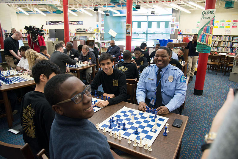 Officer Nate McCraw enjoying a chess game with public school students.