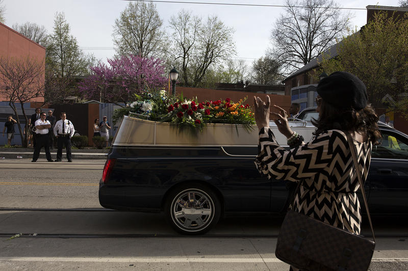 A guest takes photos of the start of the funeral procession for rock 'n' roll legend Chuck Berry. (April 9, 2017)