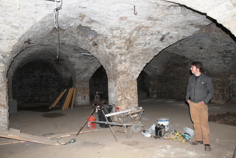 Brewmaster Stuart Keating, seen in a May 1 photo, stands in the excavated cellar below the taproom of Earthbound Brewery. It contains eight groin-vaulted arches, supported by a trio of three-foot limestone pillars..