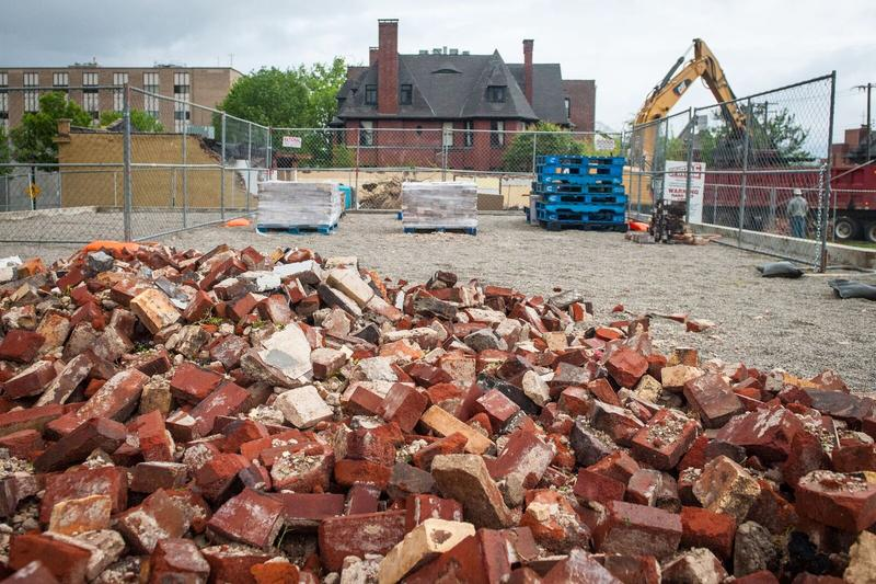 A pile of bricks sits in the left hand corner of the image while behind it rest pallets of brick and a building.