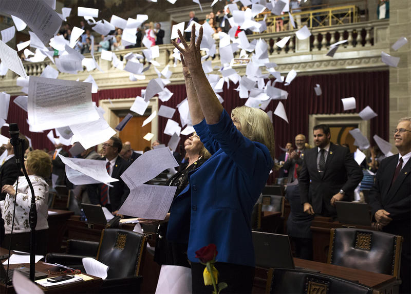 Members of the Missouri House of Representatives throw paper in the air to mark the end of the legislative session in Jefferson City.