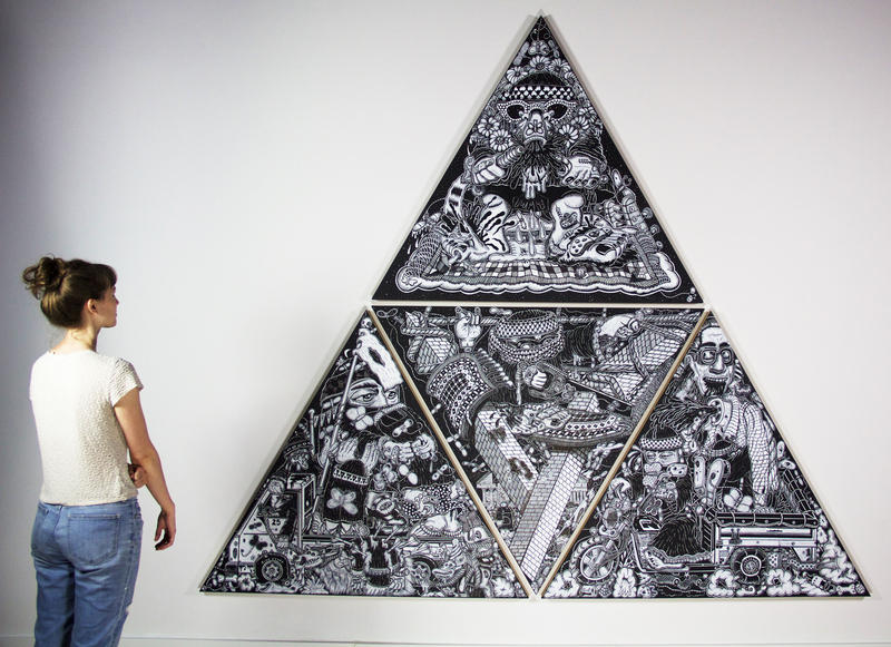A young woman stands before Edo Rosenblith's painting which is three black and white triangle panels linked to form a large triangle.