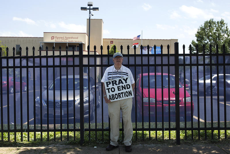 A volunteer with Coalition for Life St. Louis protests outside Planned Parenthood on Forest Park Avenue.