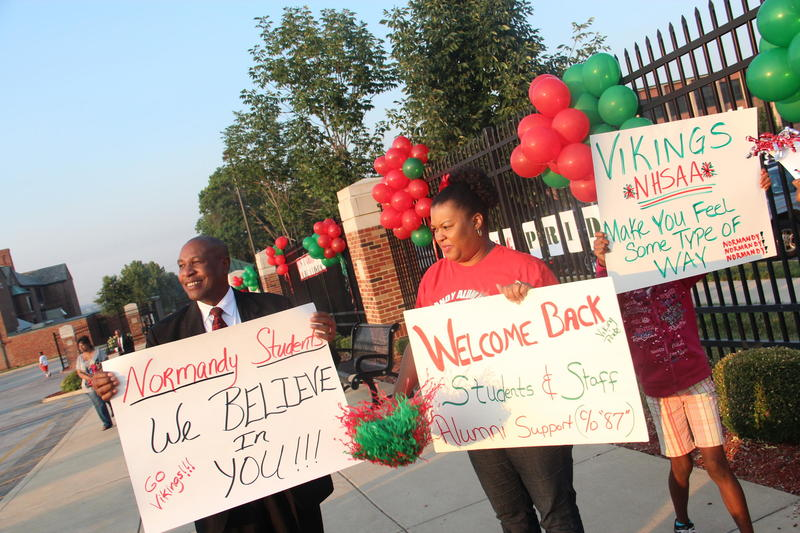 Parents and alumni wave signs welcoming students back to Normandy High School for the 2013 school year.