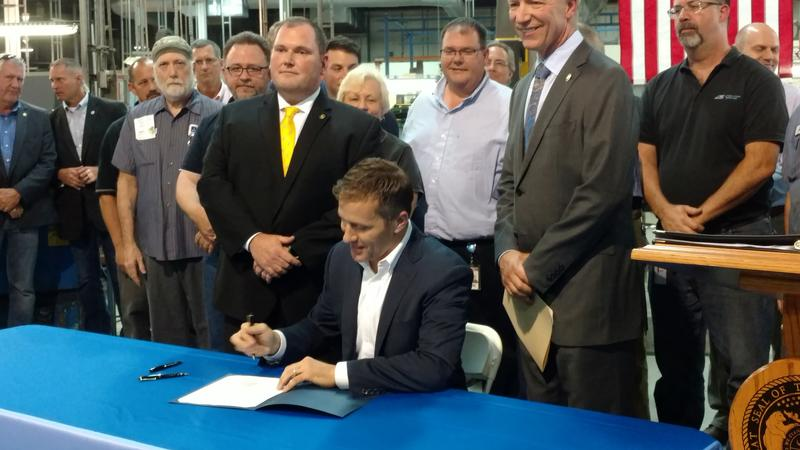 Missouri Gov. Eric Greitens signs a bill on Tues., May 30, 2017, banning project labor agreements before workers at Automation Systems, a firm in Earth City.