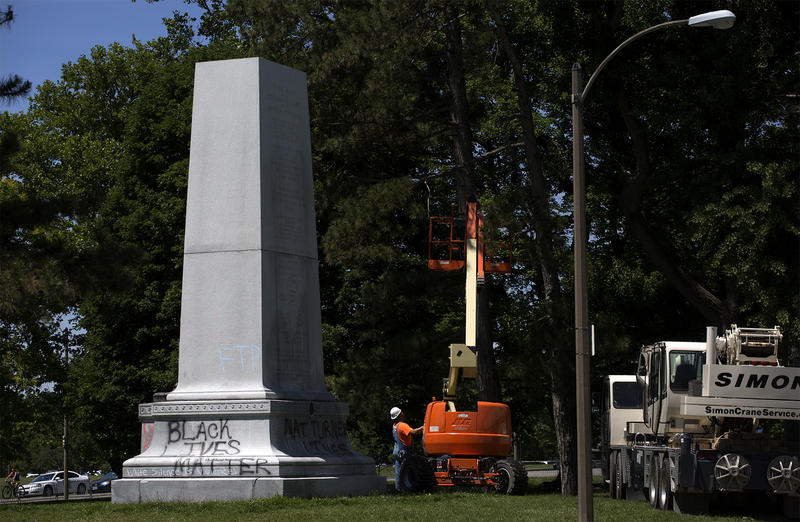 A worker adjusts a lift after the removal of the top piece of the Confederate Memorial in Forest Park last week. (June 8, 2017)
