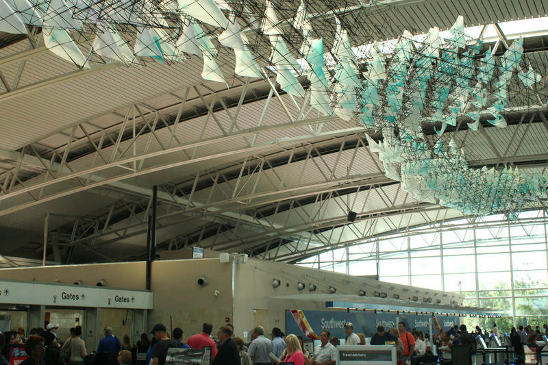 A 100-foot sculpture  made from fibers and plastic sheets hangs from the ceiling at St. Louis Lambert International Airport over the heads of Southwest Airlines passengers waiting to pass through security.