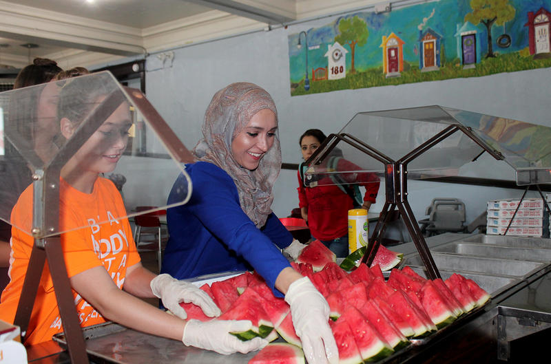 Nermana Huskic, right, and Diana Mrzljak, 15, set out watermelon before lunch at Gateway 180 June 18, 2017.