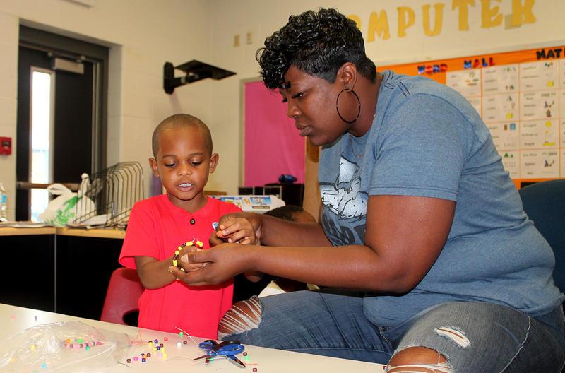 Head Start teaching assistant Shavonda Willis helps Jemez Jackson Harris IV close a bracelet he made to practice patterns June 23, 2017.