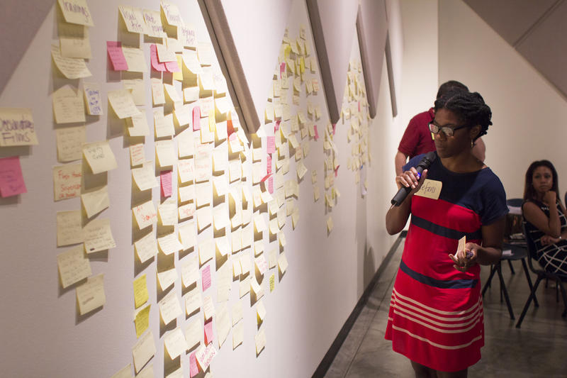 An artist or advocate stands before a wall of sticky notes at RAC in 2014 artists and advocates gathered at RAC to discuss the roll of the artist in social justice movements following the shooting death of Michael Brown Jr.