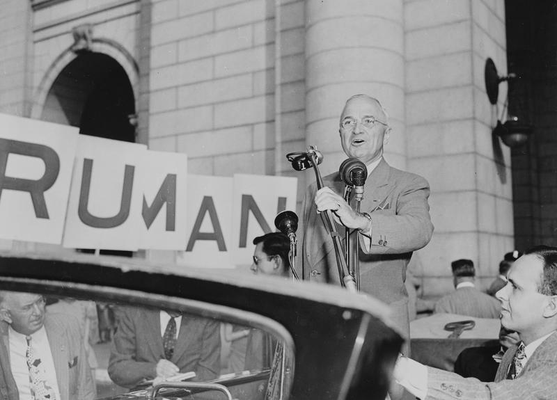 President Harry S. Truman standing in an open car, speaking into microphones in 1948, Washington, DC. President Truman had just returned from a campaign trip.
