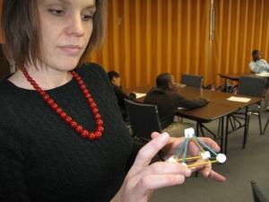 Kristi Meyer,KIPP KC math teacher, demonstrates how 5th graders use small marshmallows and toothpicks to understand vertices, ends and geometric shapes.