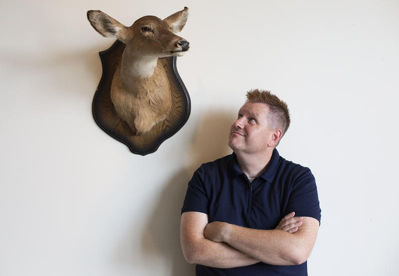 Matthew Kerns poses for a portrait with his late father's mounted deer head. The head, of the first deer his father killed, is now his prized possession. July 2017.