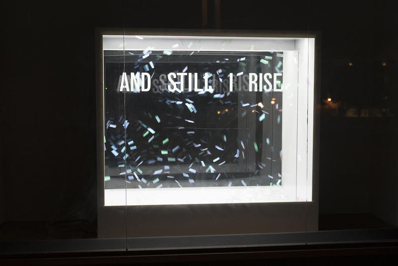 Confetti hangs in an open window reminiscent of a snowglobe in Bunny Burson's sculpture