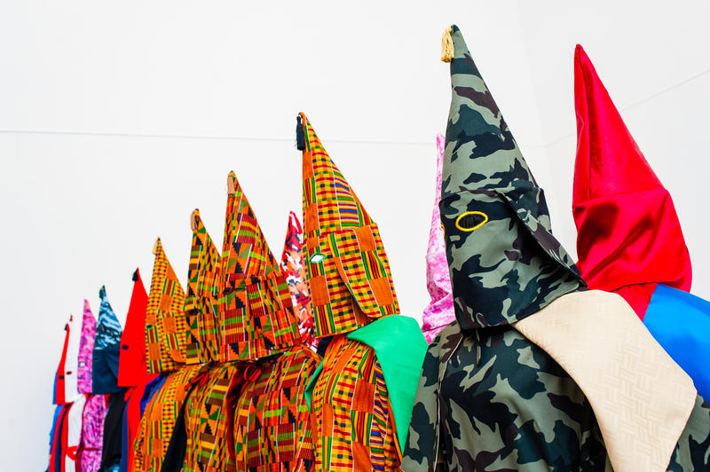 Still from an earlier iteration of Rewind depicts Klu Klux Klan robes in Kente cloth, camoflage, and other fabrics as an attempt to reclaim rascist iconography.