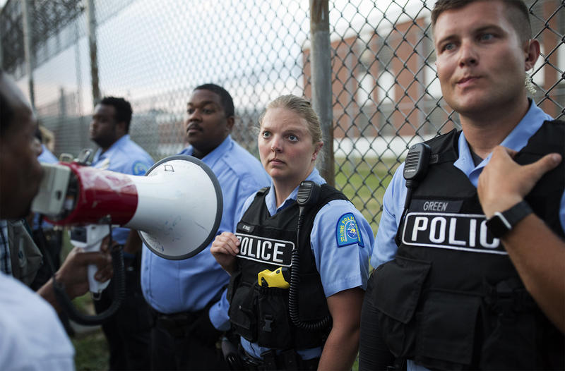 Police line up against the Workhouse fence to prevent protesters from shaking it. July 21, 2017.