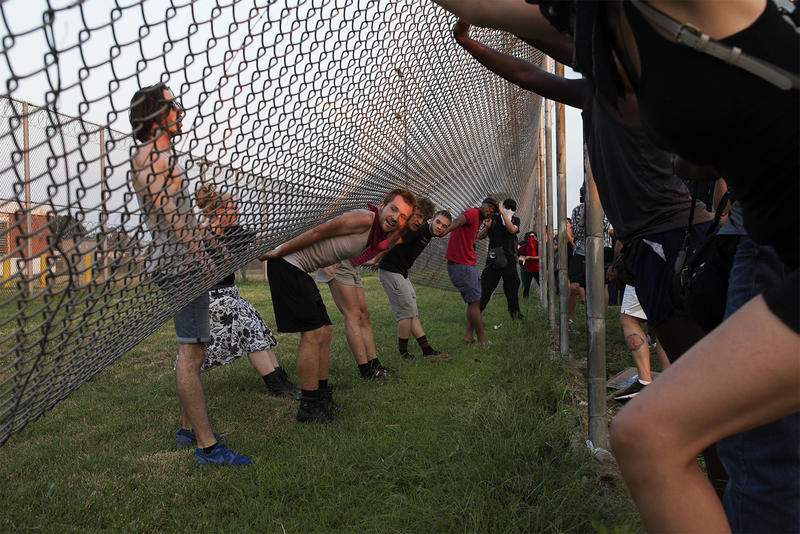 Protesters push and lift one of the fences surrounding the St. Louis Medium Security Institution. (July 22, 2017)