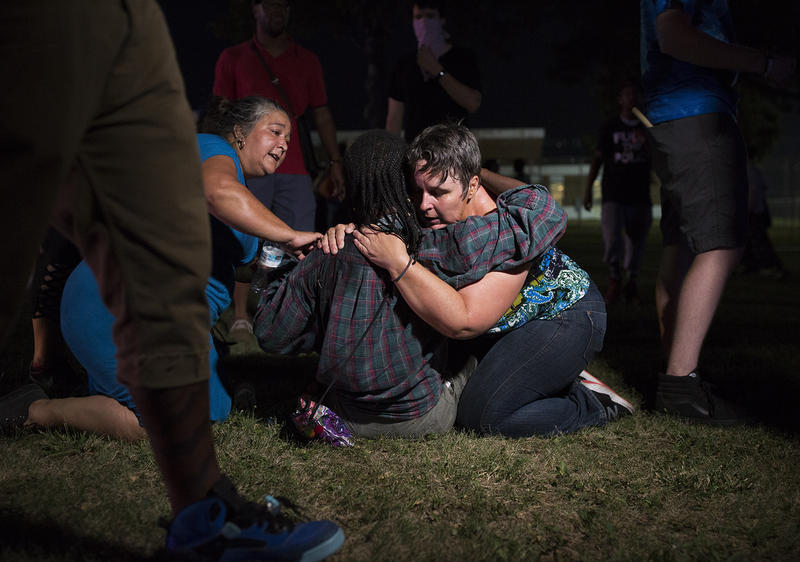 Activists comfort a friend who was sprayed with a chemical agent.