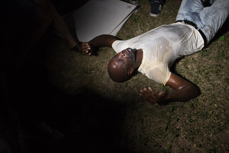 Chris Phillips, a documentary filmmaker, lays on the ground after police sprayed chemicals into the crowd.