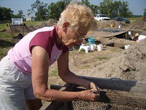 Rita Cooper, 67, examines pieces of clay and stone retained by the half-inch screen she used to filter dirt. 2008 photo 300 pals