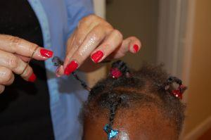 braiding a young African-American girl's hair 300 pxls 2008