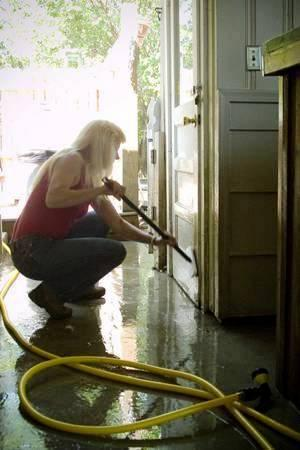 Diane Hays helps get the outside clean, as the inside of the house waits for FEMA. 300 pixels 2008