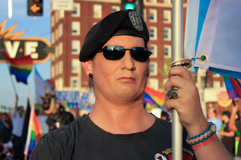Michelle Daytona, a transgender U. S. Army veteran, held a transgender flag as hundreds of protesters chanted behind her on July 30. The rally was in response to President Donald Trump's tweets announcing a ban on transgender troops.