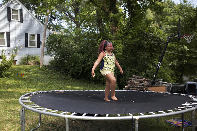 Mazy Gilleylen bounces on a trampoline outside her home in Overland. Summer 2017.