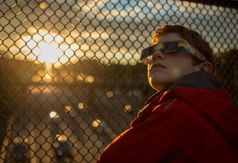 12-year-old Alex Frye checks his special viewing glasses prior to viewing the partial solar eclipse from a highway overpass in Arlington, Virginia, Thursday, Oct. 23, 2014.