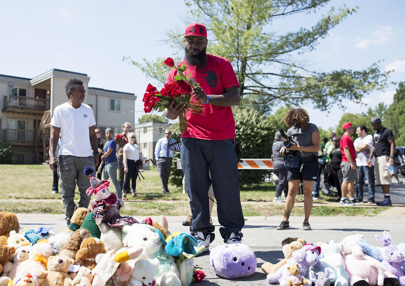 Michael Brown Sr. places roses along Canfield Drive before the start of a moment of silence for his son, Michael Brown.