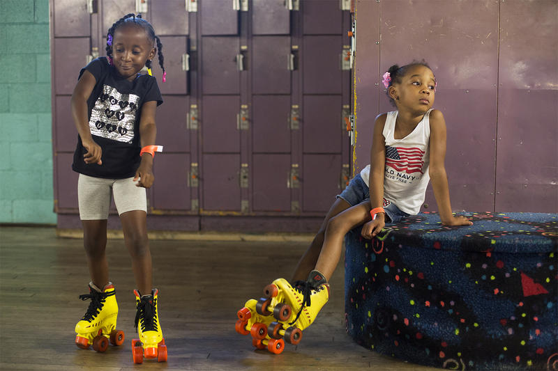 Ke'Moni Mitchell, 6, dances while Shanaya Harris, 5, takes a break from skating at the Korey Johnson Foundation's Can Skate night.