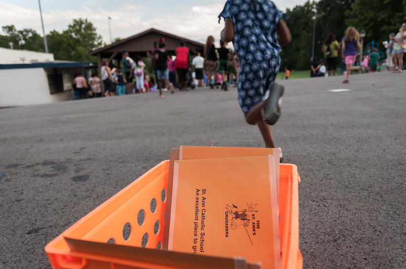 Children run past a box of welcome packets at new parent orientation at St. Ann Catholic School in Normandy on Aug. 10, 2017.