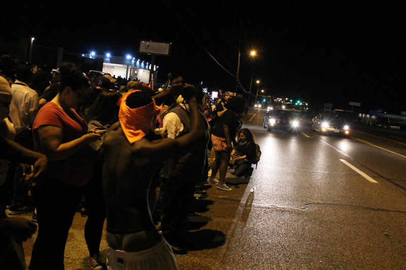 People line the sides of West Florissant during a protest held to marke the one year anniversary of Michael Brown's death.