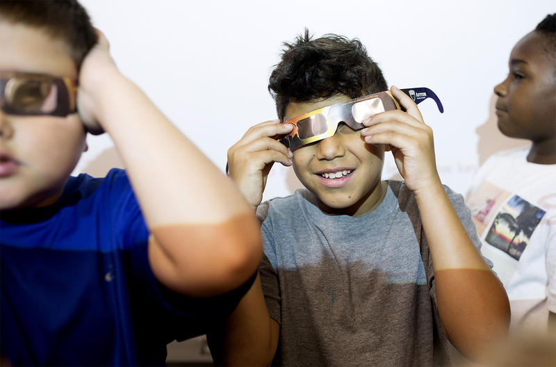 Third-grader Donoven Cruz tries out his eclipse glasses with classmates while looking up at a projector light at Gotsch Intermediate School in Affton. Aug. 17, 2017
