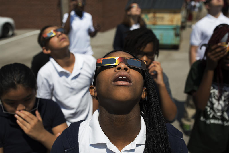 Joyetta White looks up at the partial eclipse with classmates at Long International Middle School in St. Louis.
